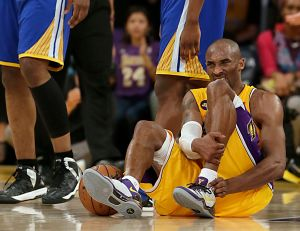 Kobe Bryant writhes in pain on the court late in the game against the Warriors at Staples Center.